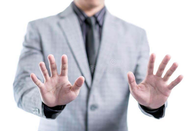 El hombre de negocios en traje gris está mostrando sus dos manos para parar algo imagenes de archivo