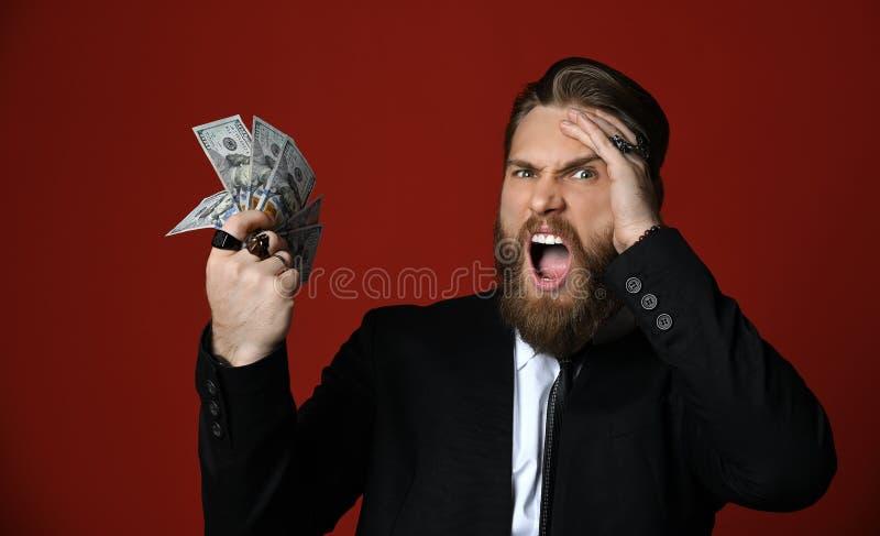El hombre de negocios en traje negro lleva a cabo billetes de banco americanos y gritos de los centenares de los dólares en alta  fotografía de archivo libre de regalías