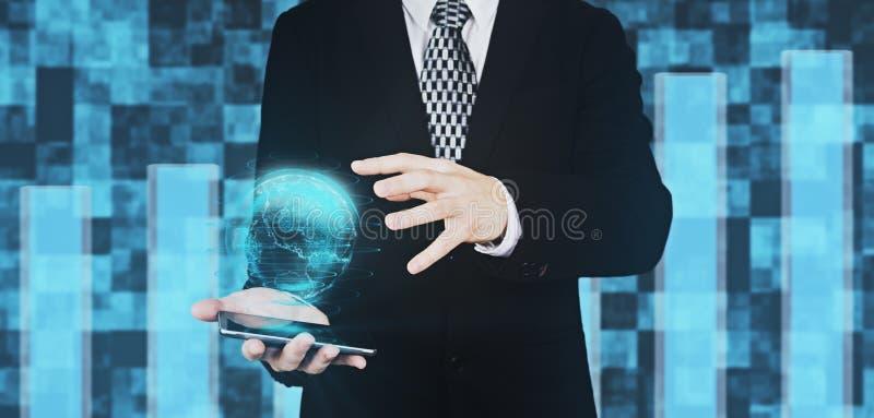 El hombre de negocios en el traje negro que sostiene Smartphone a disposición mientras que proyecta el globo Hud Interface And Ho fotos de archivo