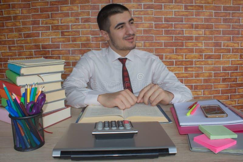 El hombre de negocios en el traje que se sienta en el escritorio en oficina delante de una pila de negocio reserva estudiar la in fotografía de archivo