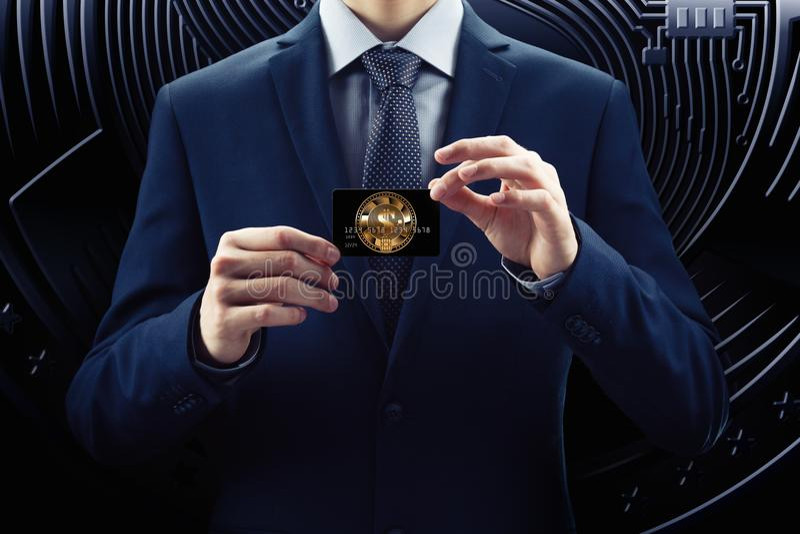 El hombre de negocios en traje y la corbata sostienen la tarjeta de crédito, con cryptocurrency Moneda del pedazo de la cadena de fotografía de archivo libre de regalías