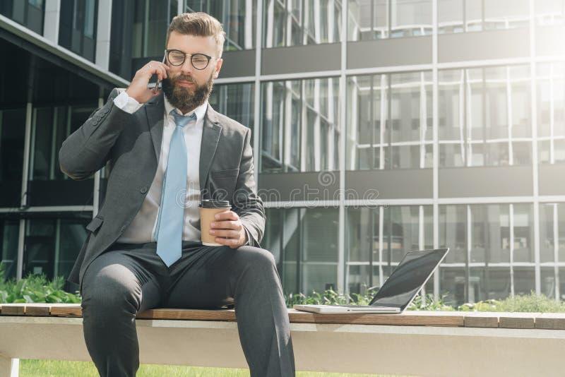El hombre de negocios en traje y lazo se está sentando afuera en el banco, café de consumición y está hablando en su teléfono cel fotografía de archivo