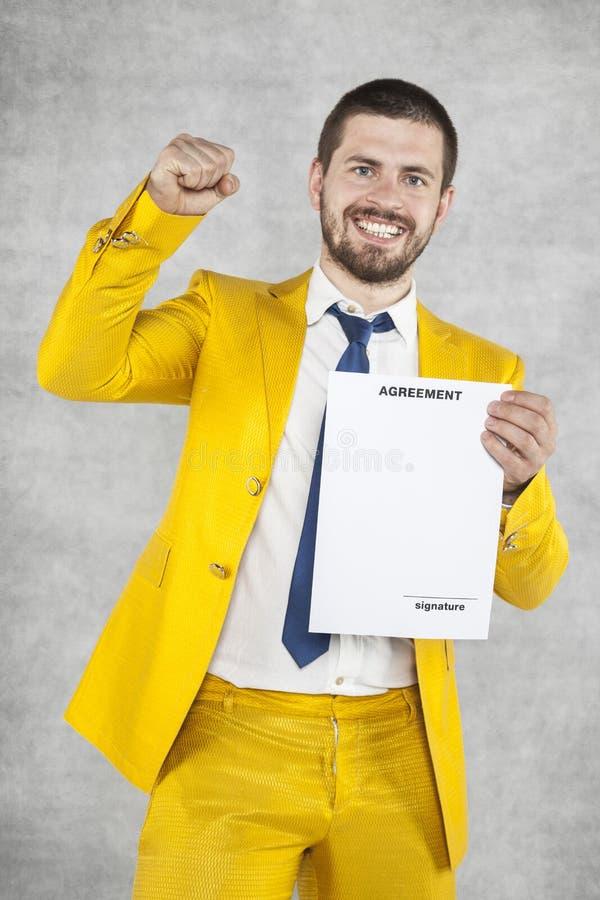 El hombre de negocios en un traje del oro es acertado, un nuevo contrato fotos de archivo libres de regalías