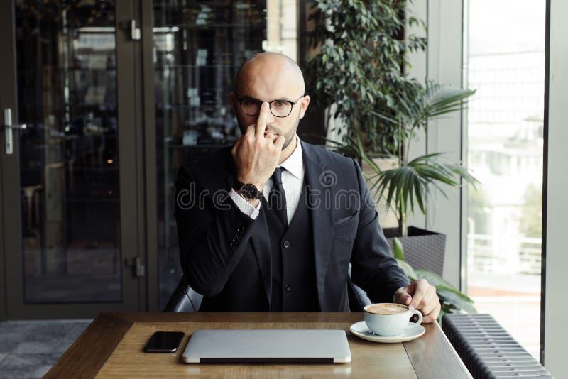 El hombre de negocios en un traje negro ajusta sus vidrios con su finger fotografía de archivo