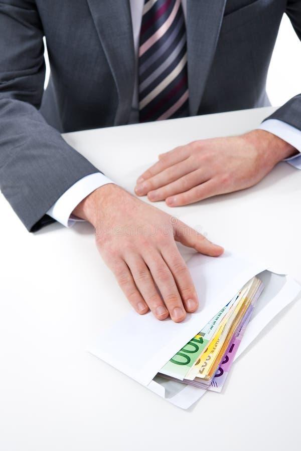 El hombre de negocios en un traje toma un soborno foto de archivo libre de regalías