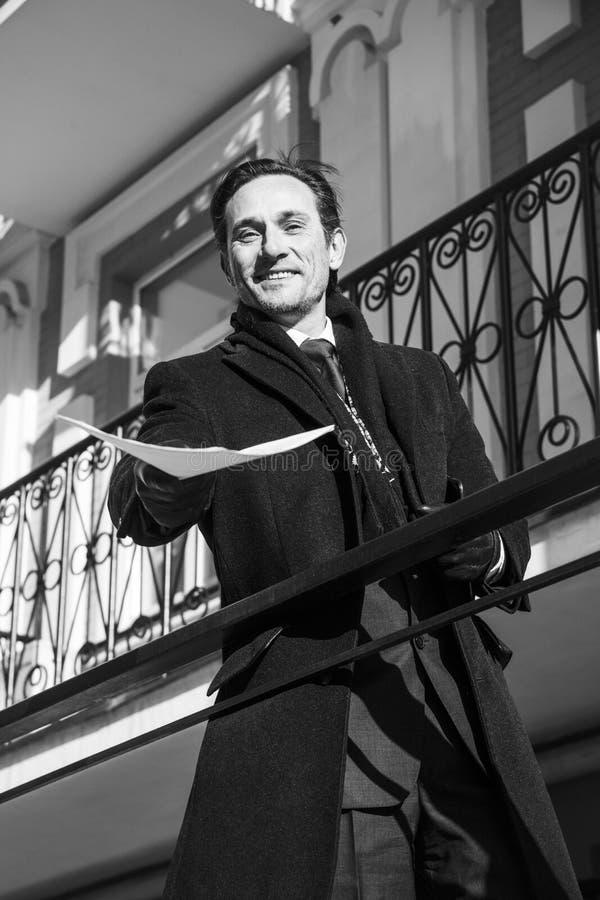El hombre de negocios en una capa oscura muestra los papeles, día, al aire libre foto de archivo