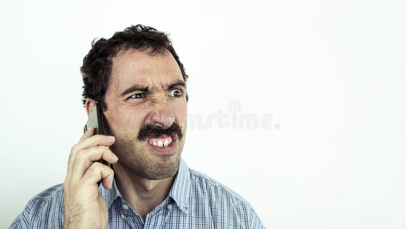 El hombre de negocios enojado con el bigote está hablando en el teléfono fotos de archivo libres de regalías