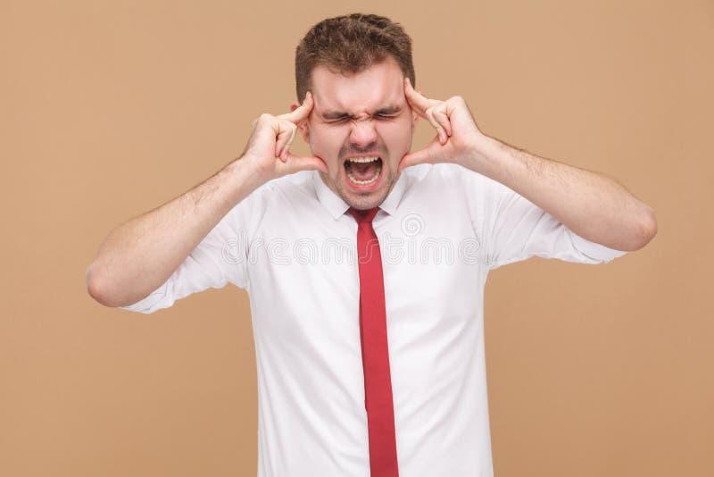El hombre de negocios enojado tiene jaqueca y dolor de cabeza foto de archivo