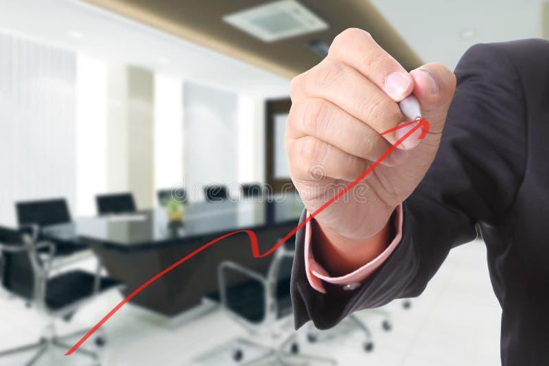 El hombre de negocios escribe el gráfico cada vez mayor para el caso de demostración imágenes de archivo libres de regalías