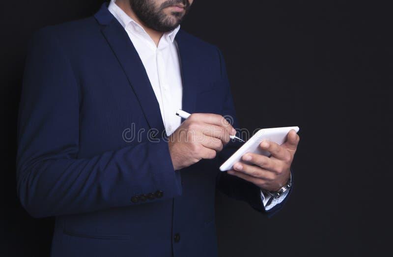 El hombre de negocios escribe en la tableta fotos de archivo