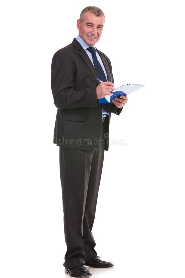 El hombre de negocios escribe en su tablero foto de archivo