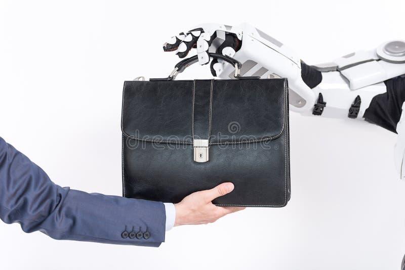 El hombre de negocios está dando su cartera al robot foto de archivo