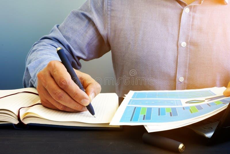 El hombre de negocios está escribiendo avisos en la libreta Trabajo con los documentos financieros imagen de archivo