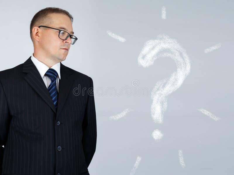 El hombre de negocios está mirando el signo de interrogación dibujado tiza fotos de archivo libres de regalías