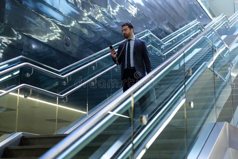 El hombre de negocios está mirando su teléfono móvil imagen de archivo libre de regalías