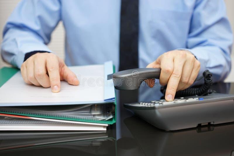 El hombre de negocios está pidiendo ayuda cuando está recibido mucho docume foto de archivo