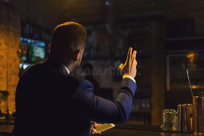 El hombre de negocios está pidiendo la cerveza en barra fotografía de archivo