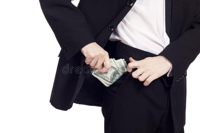 El hombre de negocios está poniendo el dinero en su bolsillo fotografía de archivo libre de regalías