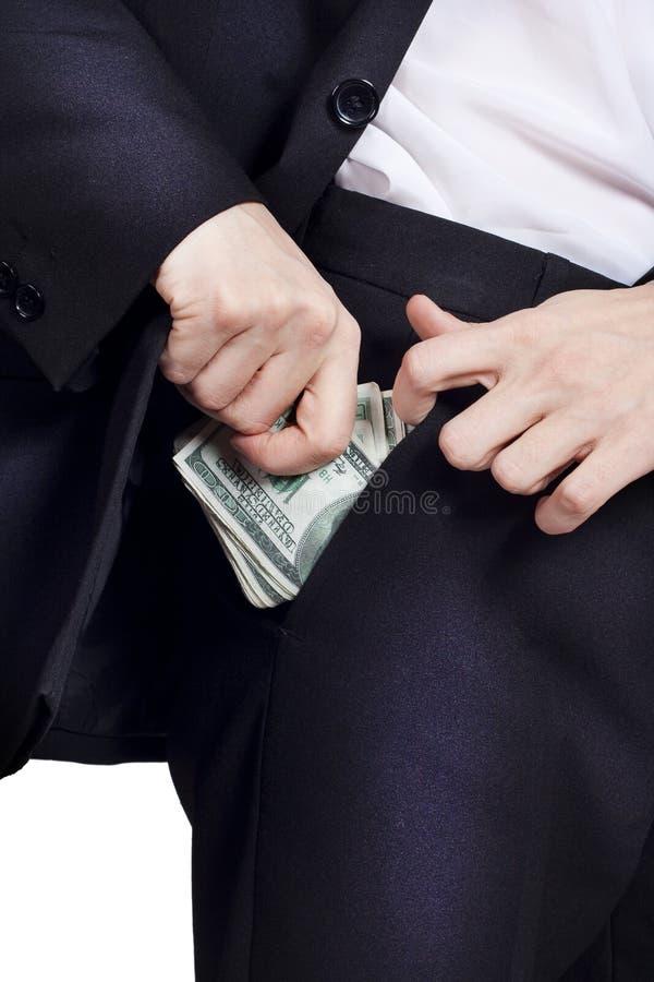 El hombre de negocios está poniendo el dinero en su bolsillo fotografía de archivo