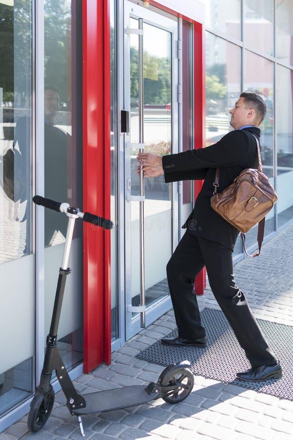 El hombre de negocios está tirando de la puerta foto de archivo libre de regalías