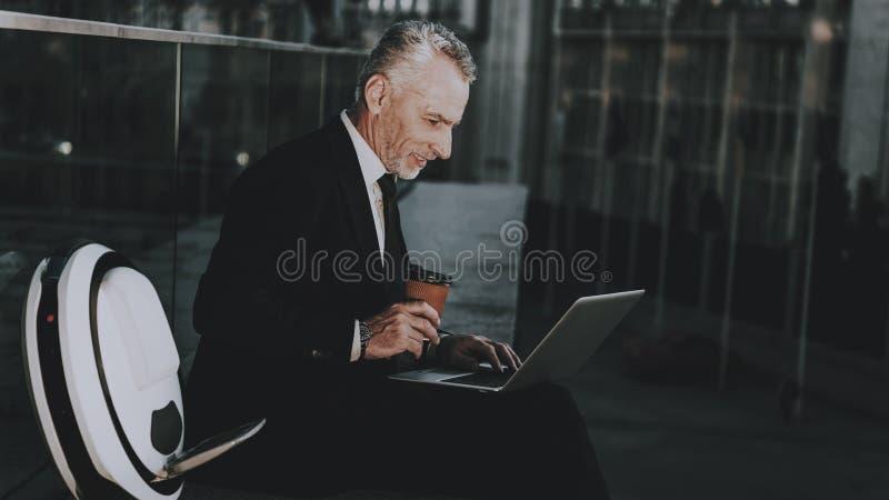 El hombre de negocios está utilizando un ordenador portátil fotos de archivo