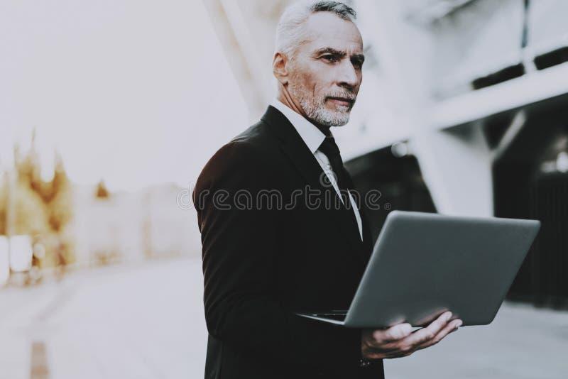 El hombre de negocios está utilizando un ordenador portátil foto de archivo