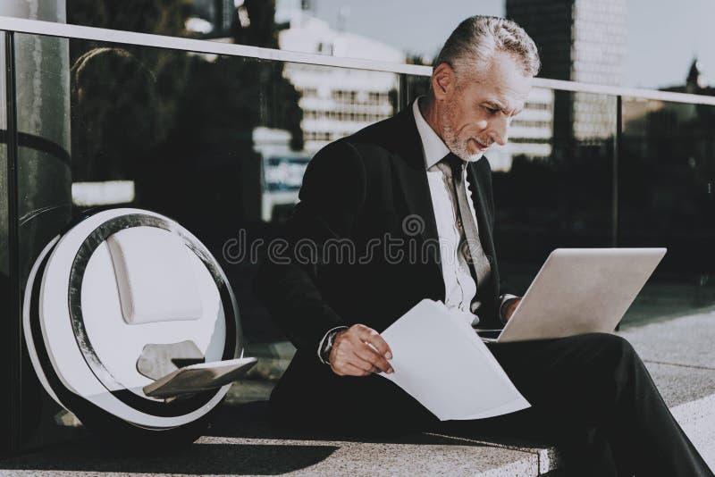 El hombre de negocios está utilizando un ordenador portátil imagenes de archivo