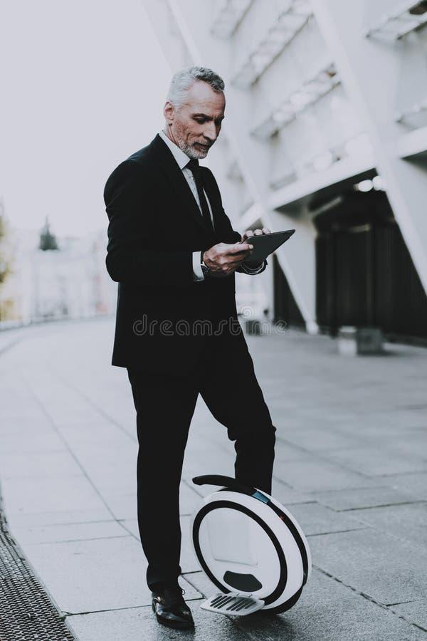 El hombre de negocios está utilizando un Tablet PC en Monowheel imágenes de archivo libres de regalías