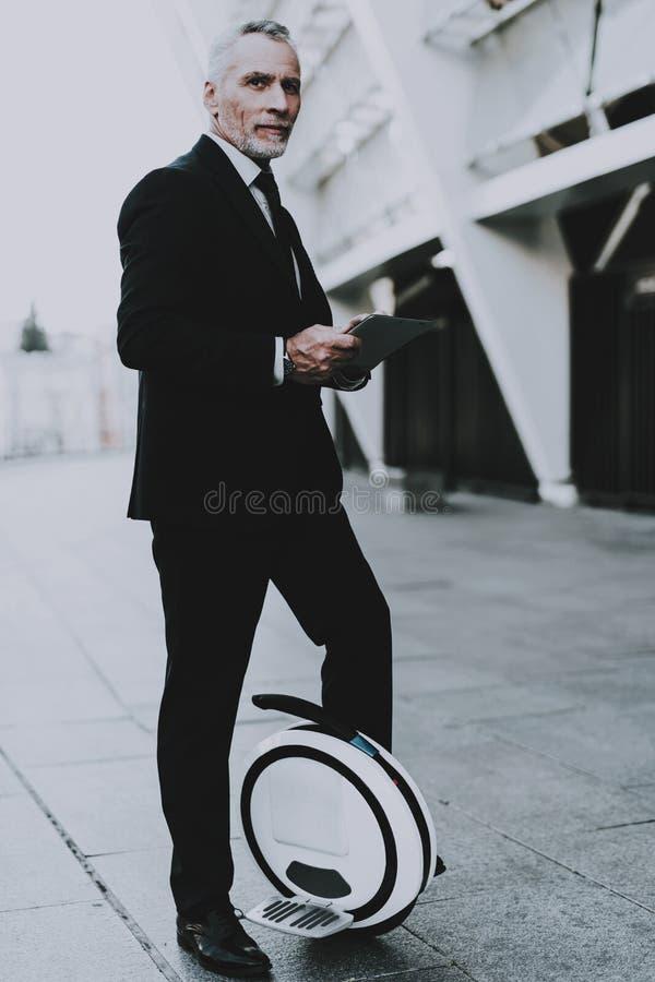 El hombre de negocios está utilizando un Tablet PC en Monowheel fotos de archivo libres de regalías