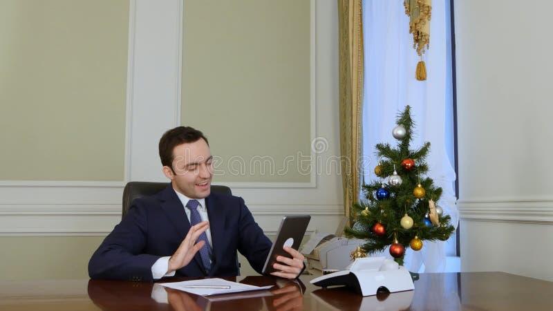 El hombre de negocios felicita a socios comerciales con la Navidad vía Internet con la tableta imagenes de archivo