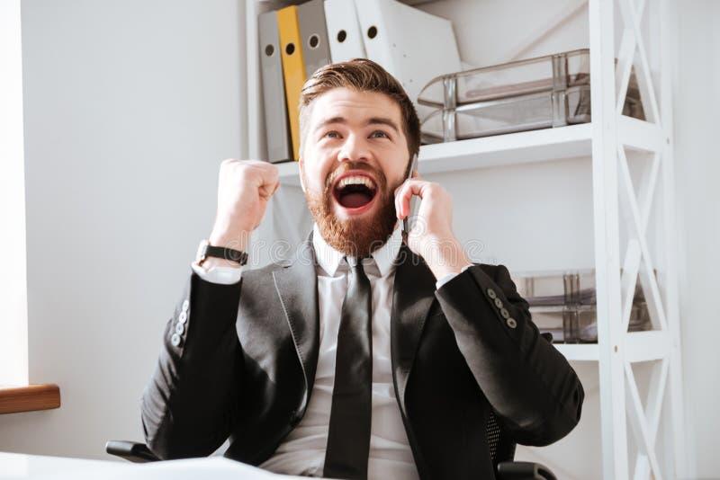 El hombre de negocios feliz que habla por el teléfono y hace gesto del ganador imagen de archivo