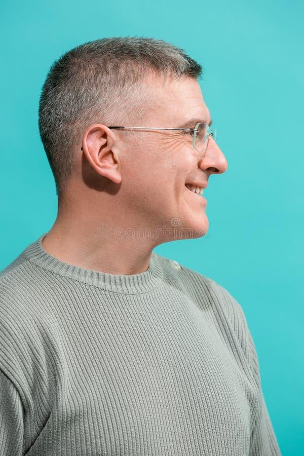El hombre de negocios feliz que se opone y que sonríe contra fondo azul imágenes de archivo libres de regalías