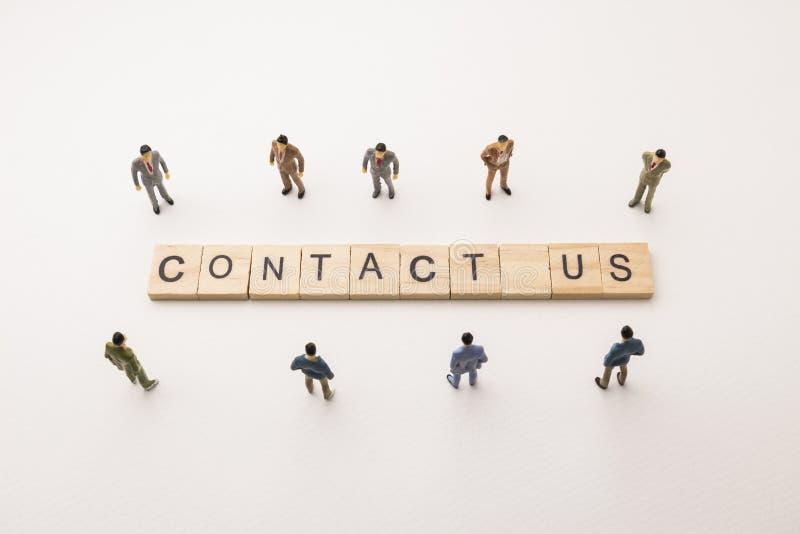 El hombre de negocios figura la reunión sobre contacto nosotros conceptuales imagen de archivo libre de regalías