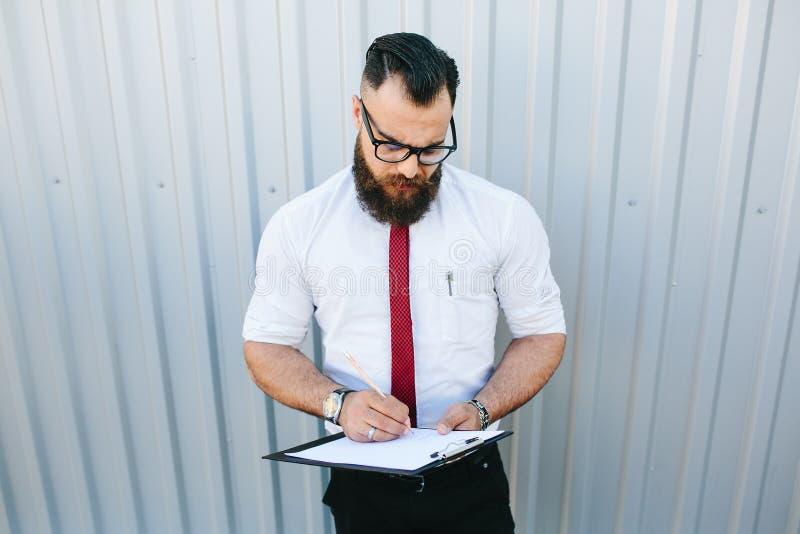El hombre de negocios firma un documento imagenes de archivo