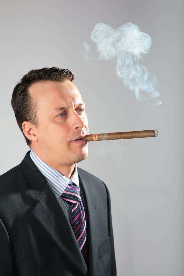 El hombre de negocios fuma el cigarro imagen de archivo libre de regalías
