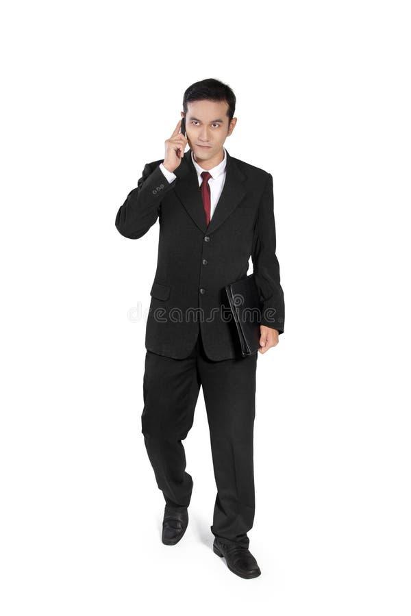 El hombre de negocios hace caminar de la llamada de teléfono imagen de archivo