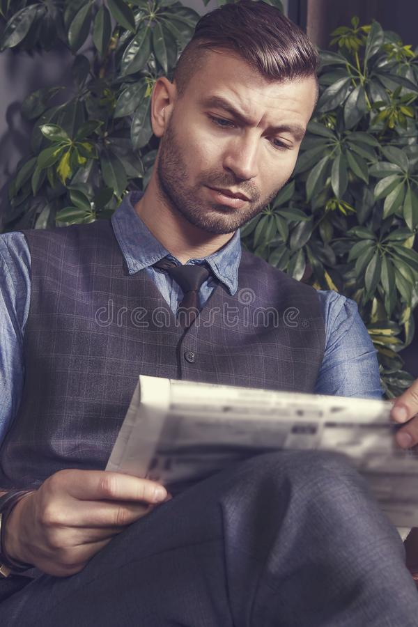 El hombre de negocios hermoso brutal de moda elegante se sienta en silla y lee noticias en periódico Retrato del hombre en traje foto de archivo libre de regalías