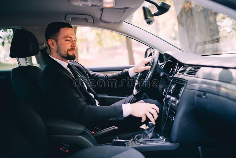 El hombre de negocios hermoso en el asiento de conductores en su coche y el cambio apresuran fotografía de archivo libre de regalías