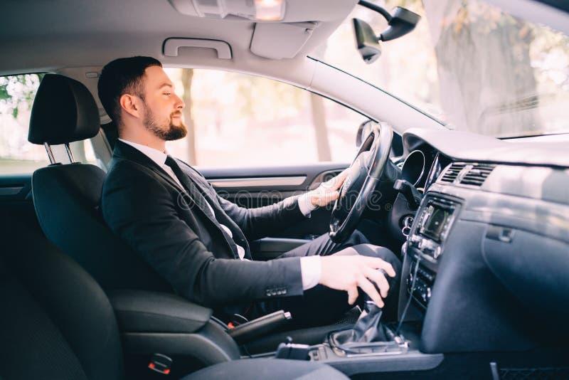 El hombre de negocios hermoso en el asiento de conductores en su coche y el cambio apresuran foto de archivo