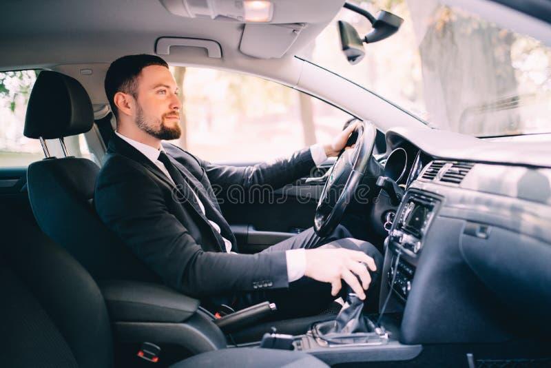 El hombre de negocios hermoso en el asiento de conductores en su coche y el cambio apresuran imágenes de archivo libres de regalías