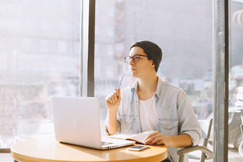 El hombre de negocios hermoso en ropa de sport y lentes está utilizando un ordenador portátil en café imagen de archivo