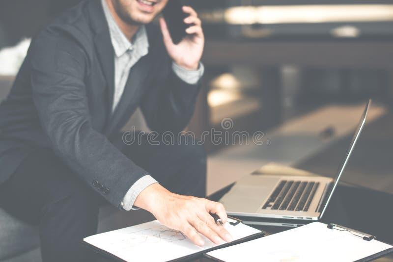 El hombre de negocios hermoso en el traje y las lentes que hablaban en el teléfono en oficina, vista lateral tiró de las manos de fotografía de archivo libre de regalías