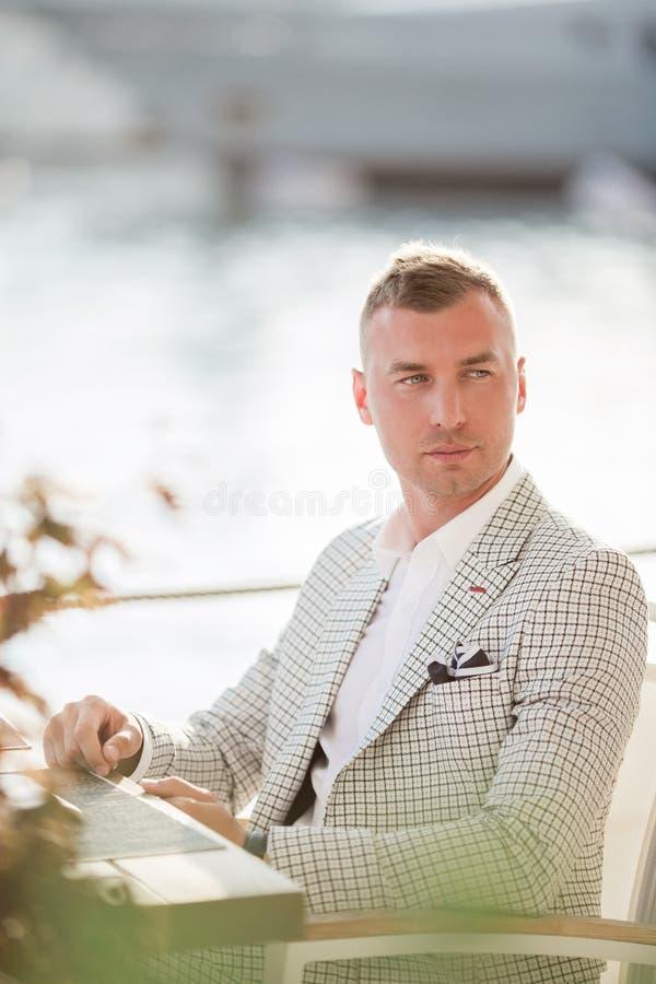 El hombre de negocios hermoso está llevando el traje blanco de la moda que se sienta en café con el fondo del mar Bah?a de Monten fotos de archivo libres de regalías