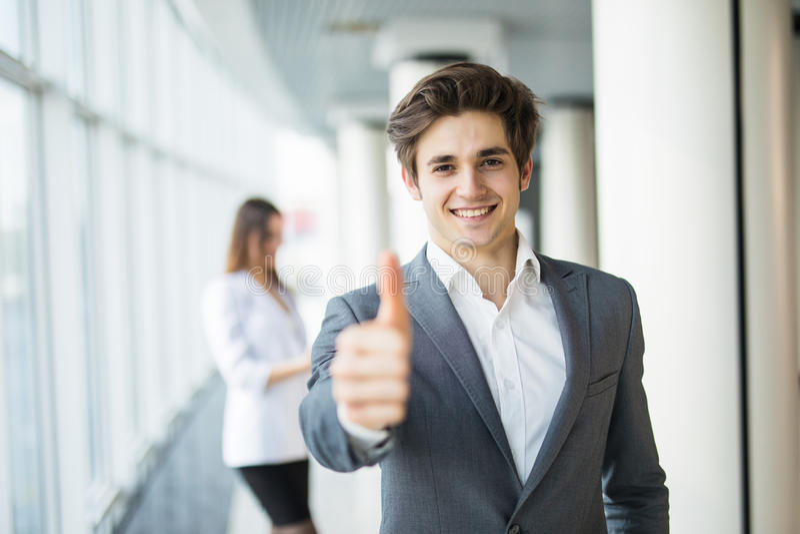 El hombre de negocios hermoso joven manosea con los dedos para arriba delante de mujer de negocios Personas del asunto foto de archivo libre de regalías