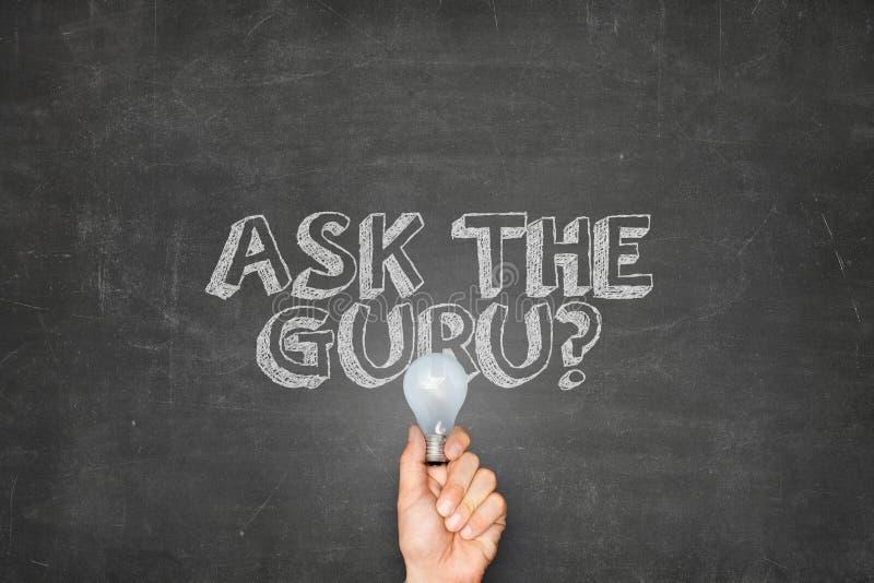 El hombre de negocios Holding Light Bulb debajo pregunta a Guru On Blackboard fotografía de archivo