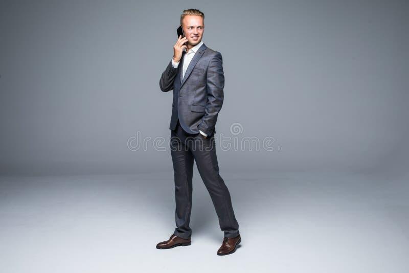 El hombre de negocios integral en traje negro se mueve con la mano en bolsillo y hablar en el teléfono Fondo gris aislado imagen de archivo