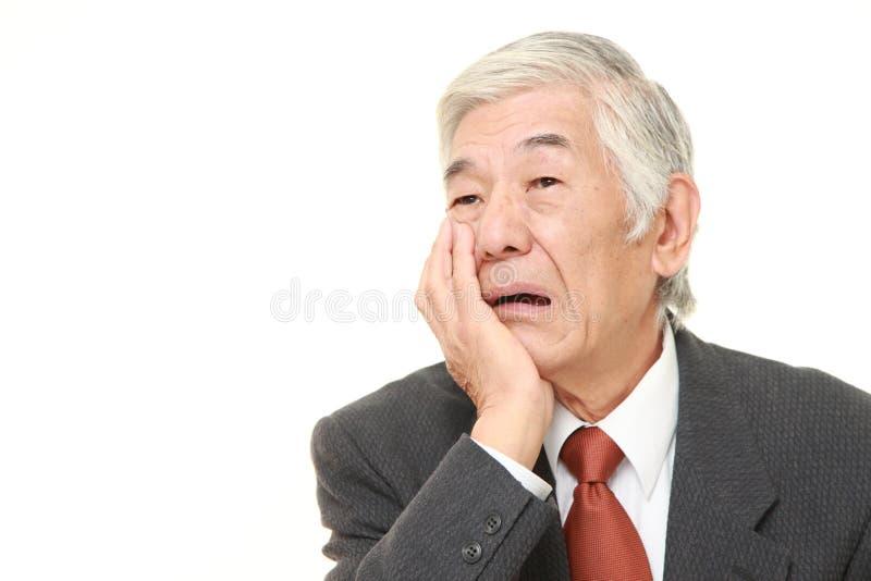 El hombre de negocios japonés mayor sufre de dolor de muelas fotos de archivo