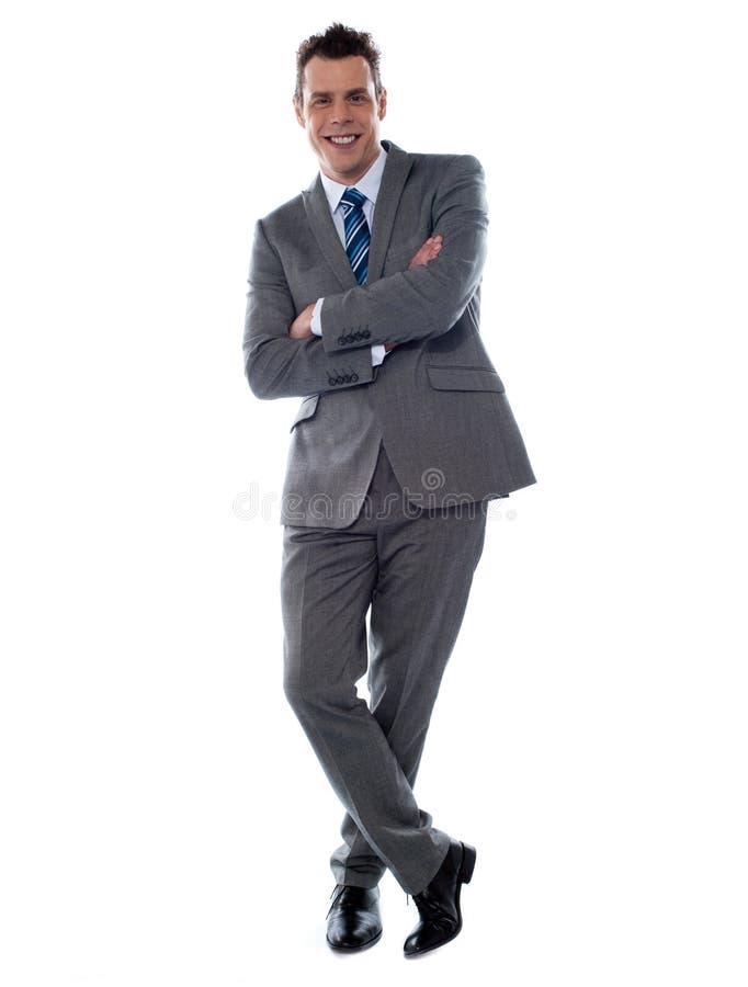 El hombre de negocios joven alegre se inclina contra la pared foto de archivo