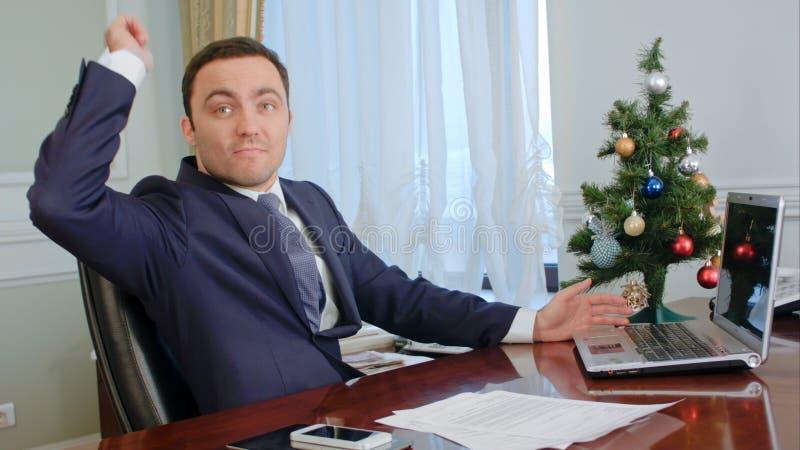 El hombre de negocios joven amenaza al opositor invisible y quiere lanzar la pluma de bola en broma, pero es tiempo de la Navidad fotos de archivo