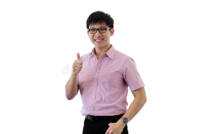 El hombre de negocios joven asi?tico tiene situaci?n con los pulgares para arriba en aislado en fondo del wihte fotografía de archivo